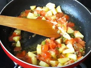 potatoes with tomato in pan