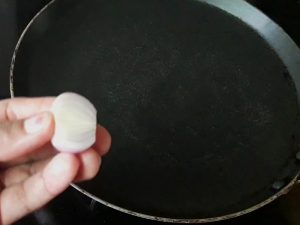 clean dosa tawa with onion or wet cloth