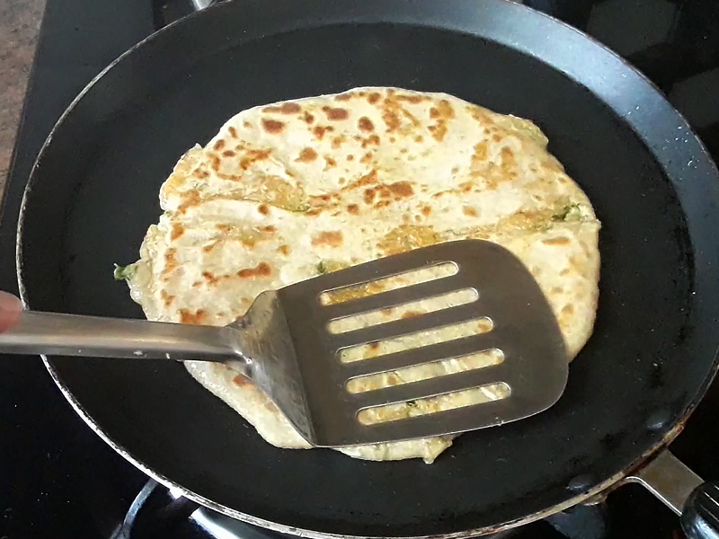 press paratha to cook it from both sides