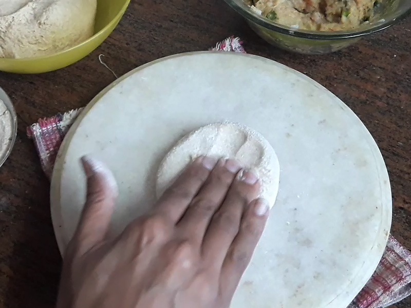 flattened dough ball with fingers