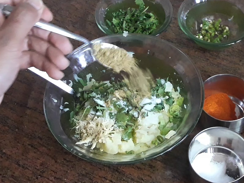 coriander powder in grated potatoes